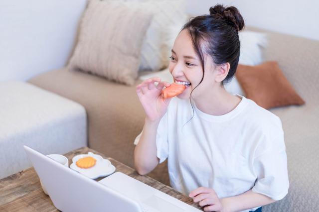 銀座みらい歯科院長コラム|口腔内PH値と唾液のはたらき|おやつを食べながらテレワークする女性