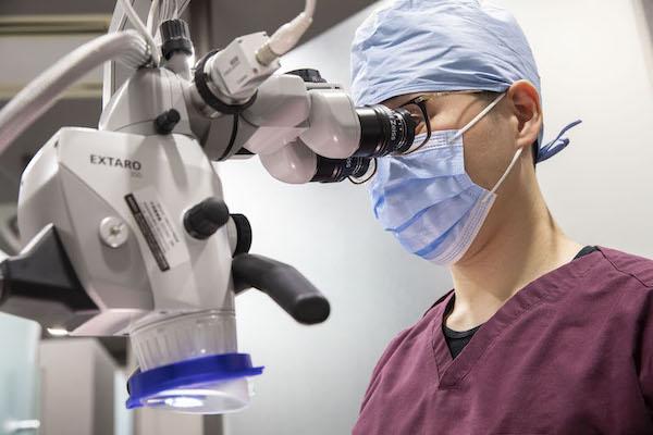銀座みらい歯科で歯科用顕微鏡(マイクロスコープ)を覗く院長