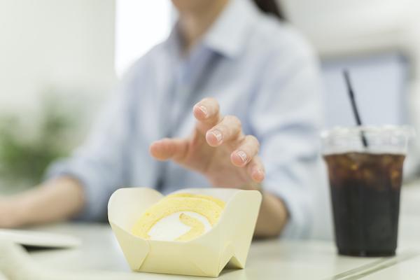 銀座みらい歯科_仕事をしながらロールケーキに手を伸ばして食べようとする女性のイメージ